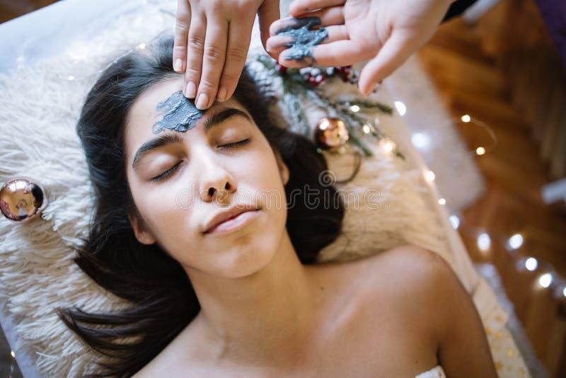 Terapista che applica una maschera sulla fronte della ragazza al salone SPA fotografia stock