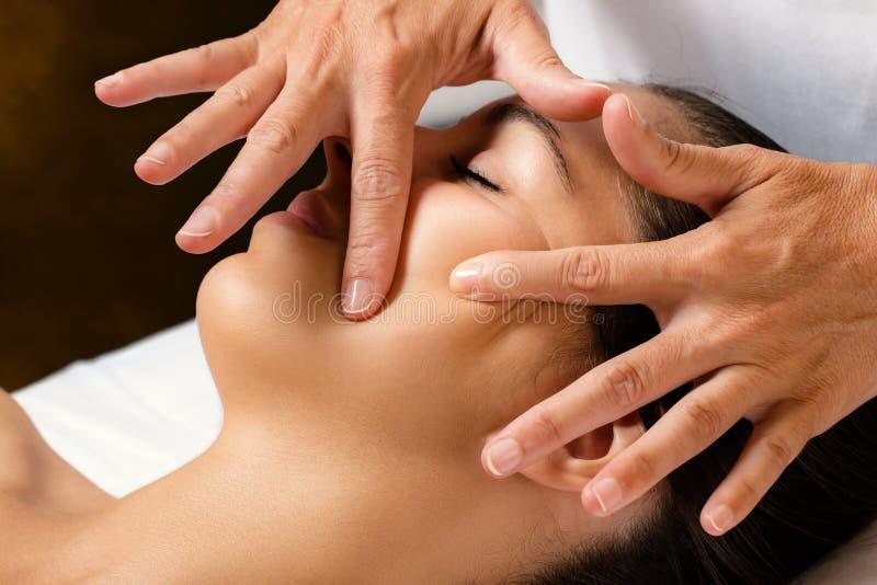 Terapista che massaggia guancia femminile immagini stock