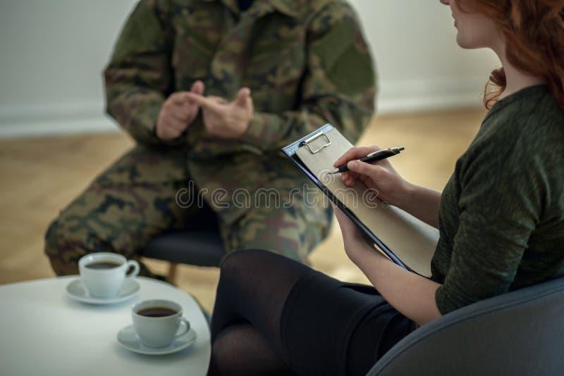 Terapista che prende le note mentre analizzando comportamento del soldato con la sindrome di guerra immagine stock