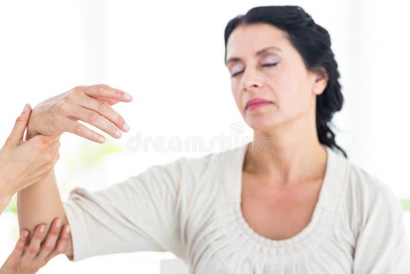 Terapista che tiene il suo braccio dei pazienti fotografie stock libere da diritti