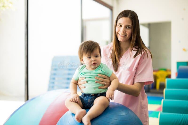 Terapista dei bei bambini sul lavoro fotografia stock