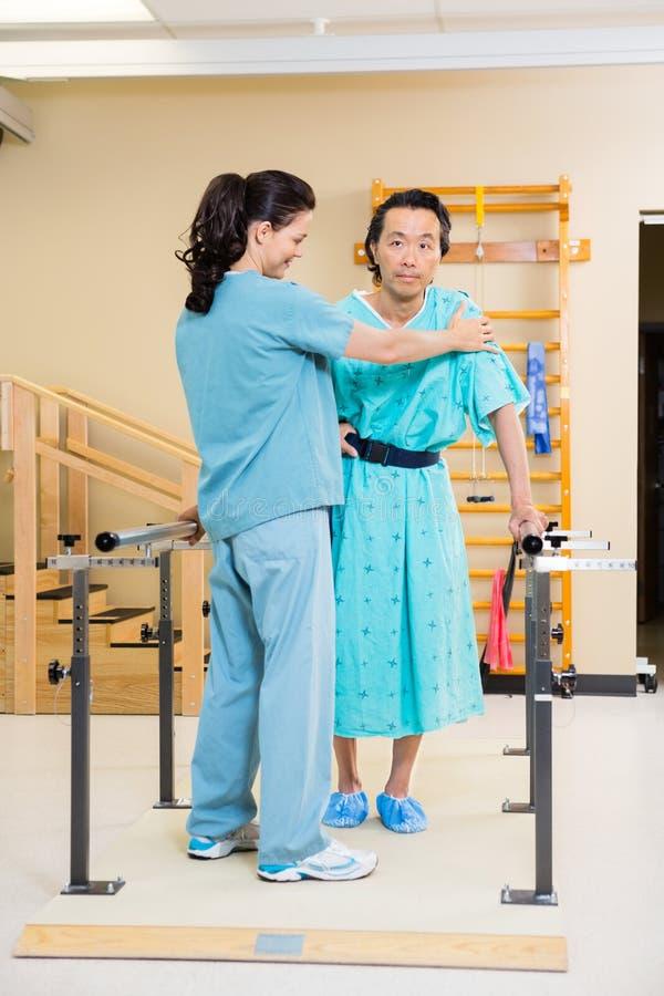 Terapista fisico Assisting Male Patient dentro fotografia stock