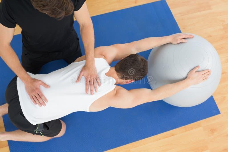 Terapista fisico che assiste giovane con la palla di yoga fotografia stock