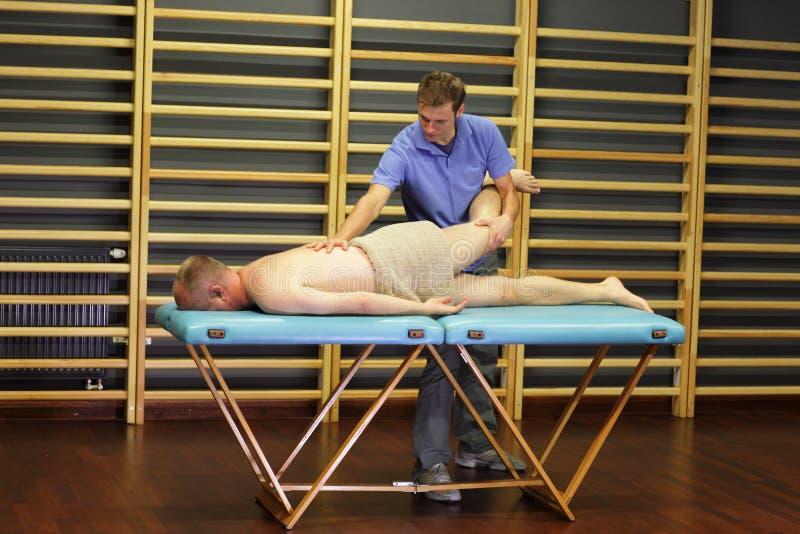 Terapista manuale che lavora con la gamba e la parte posteriore dell'uomo fotografia stock