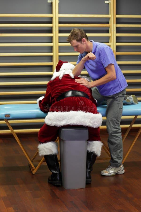 Terapista maschio che massaggia Santa Claus sovraccarica fotografia stock libera da diritti
