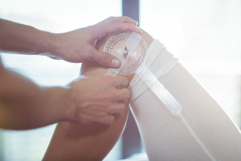 Terapista maschio che misura ginocchio paziente femminile con il righello medico immagini stock