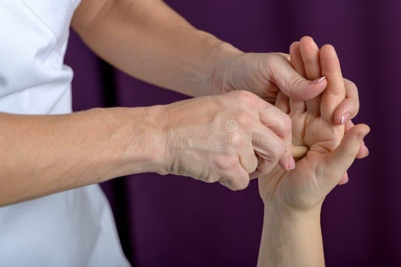 Terapista professionista di massaggio che lavora ad una mano e ad un piede della donna fotografia stock libera da diritti