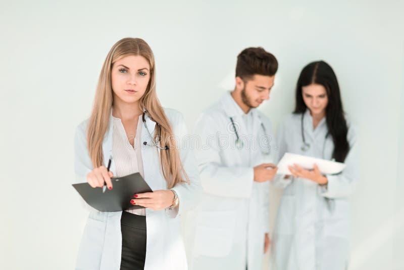 Terapista serio con una lavagna per appunti mentre stando nella clinica fotografia stock