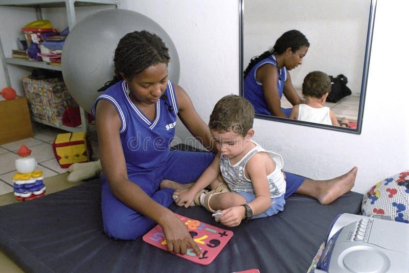 Terapista sul lavoro con il bambino handicappato, Brasile fotografie stock libere da diritti
