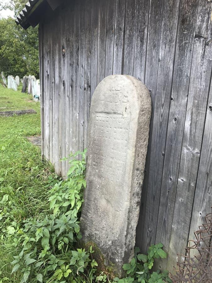 TERESVA,乌克兰, 2017年9月18日;一座老犹太公墓 在绿草中的被打碎的墓碑立场 在他们- inscrip 免版税库存图片