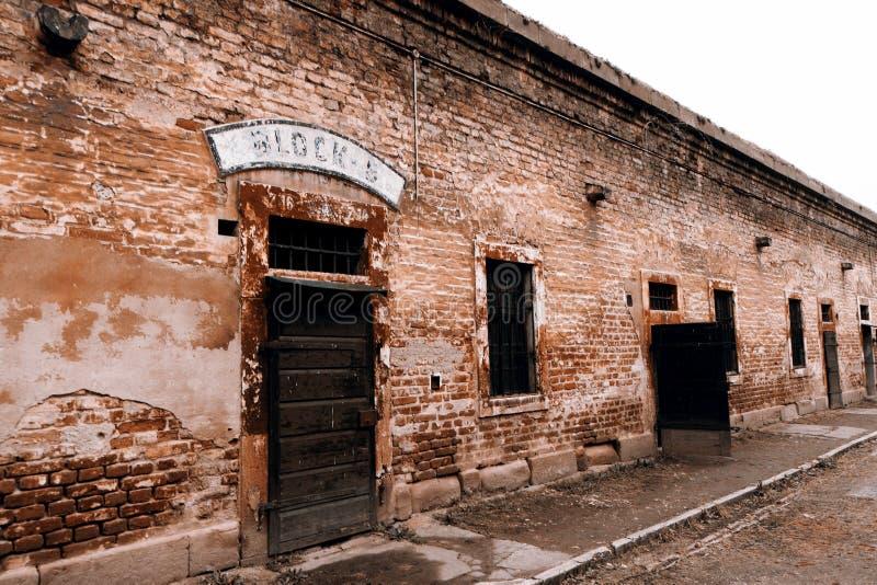 Terezin minnesmärke - gammal vägg och byggnad med kvartertecken royaltyfria bilder