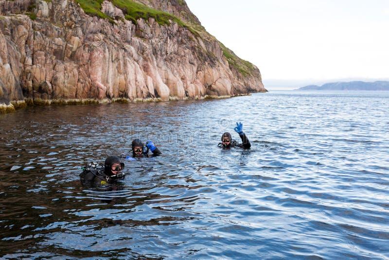 Teriberka,俄罗斯- 2017年7月29日:漂浮海的表面上的三名轻潜水员 库存照片