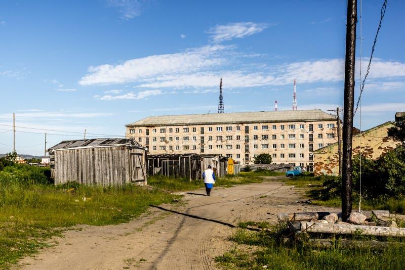 Teriberka, Россия - 25-ое июля 2017: Женщина идя вниз по улице в русскую деревню Teriberka в районе Kolsky Мурманск стоковые фото
