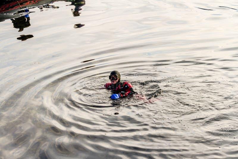 Teriberka, Rusland - Juli 27, 2017: Scuba-duiker die op de oppervlakte van het overzees dichtbij de boot drijven stock foto's