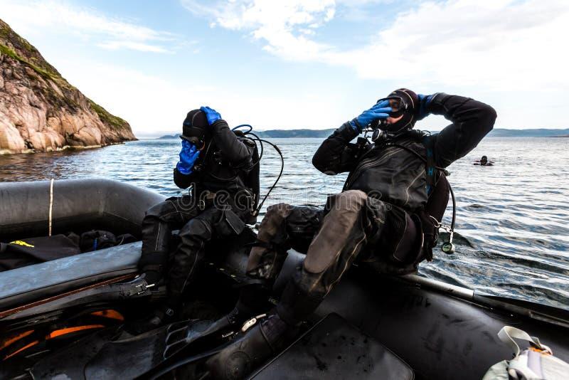 Teriberka, Russland - 29. Juli 2017: Zwei Sporttaucher, die von einem Boot in das Wasser tauchen Schuss in Barents-Meer stockbild