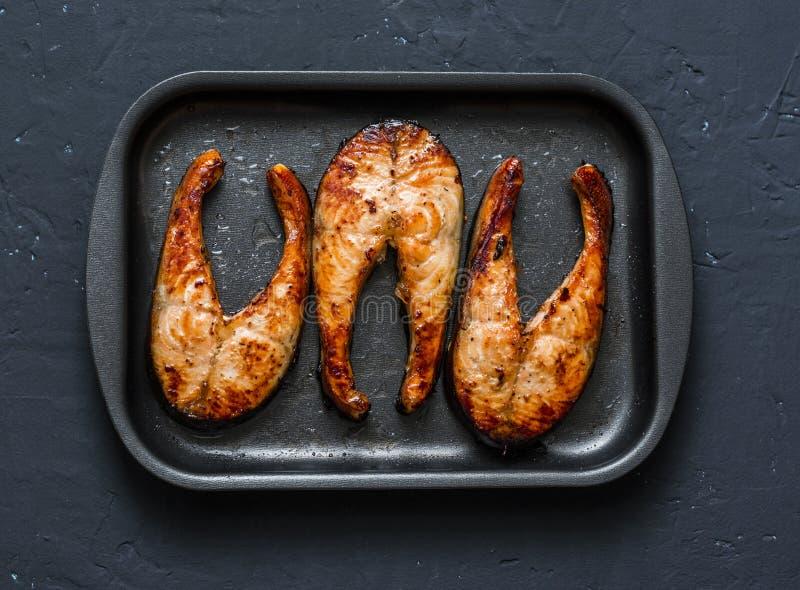 Teriyaki烘烤了在亚洲样式的三文鱼在烘烤盘子 健康油脂食物,黑暗的背景 库存图片