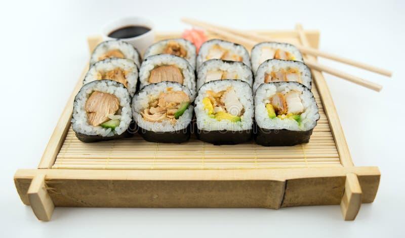 Teriyaki e rolos de sushi do frango frito na esteira de bambu japonesa com hashis, molho de soja e gengibre fotos de stock royalty free