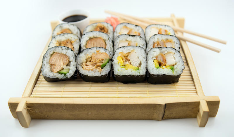 Teriyaki and fried chicken sushi rolls on Japanese bamboo mat with chopsticks, soy sauce and ginger. Traditional bamboo tray with an assortment of teriyaki and royalty free stock photos