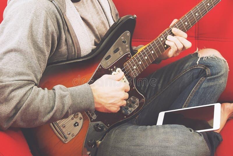 Terloops geklede jonge mens met gitaar speelliederen in de ruimte thuis Het online concept van gitaarlessen Het mannelijke gitari royalty-vrije stock foto