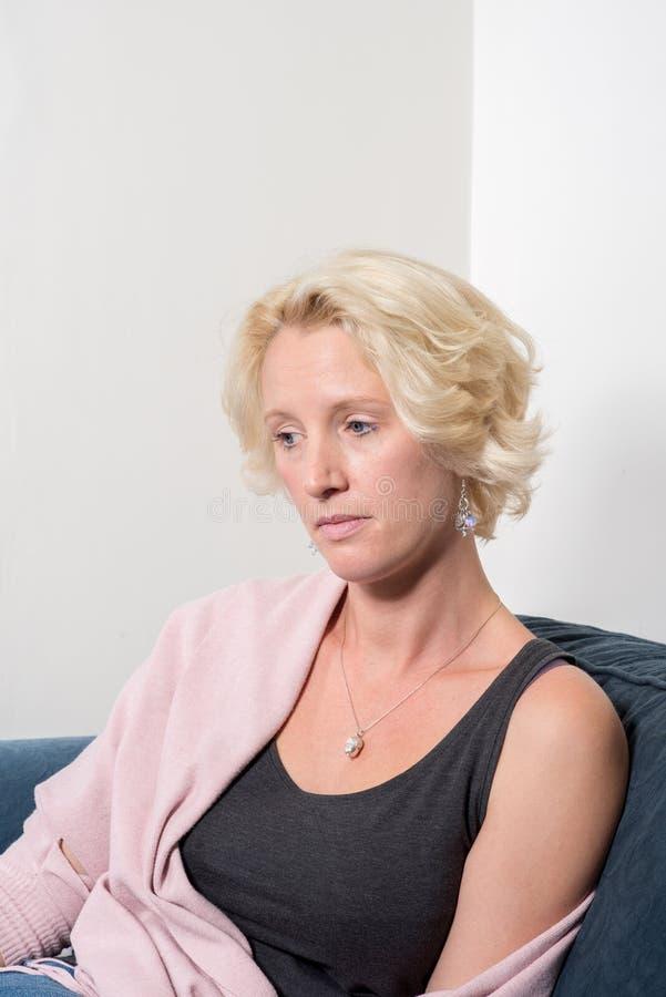 Terloops Geklede Vrouw op Sofa Stares Away Thoughtfullly royalty-vrije stock afbeelding