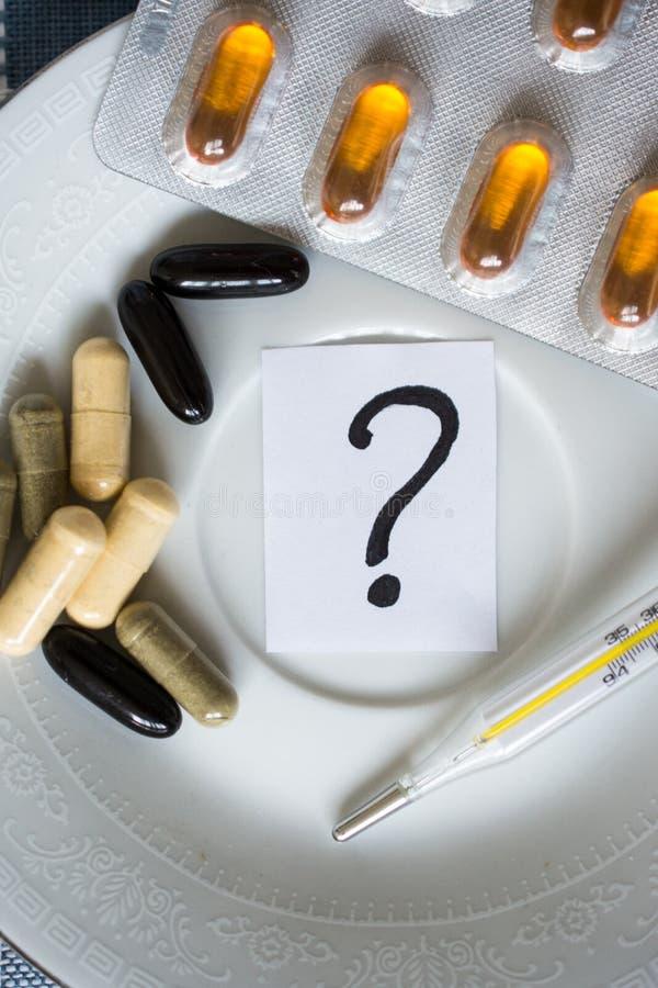 Termómetro con las píldoras en la placa y el signo de interrogación foto de archivo libre de regalías