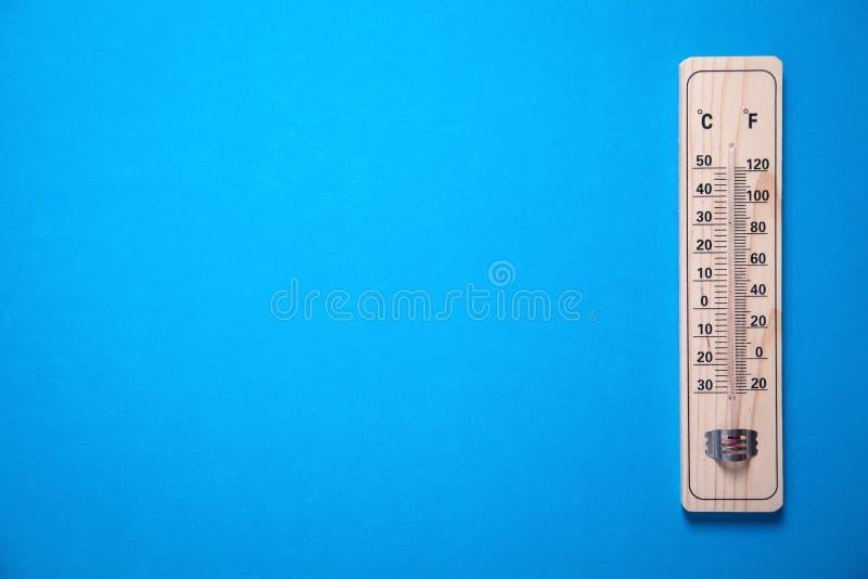 Termómetro de madera en fondo azul imagenes de archivo