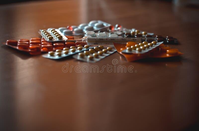 Termómetro de mercurio del vintage entre las tabletas y las píldoras multicoloras Macro Tiroteo en el nivel del ojo Foco suave imagen de archivo