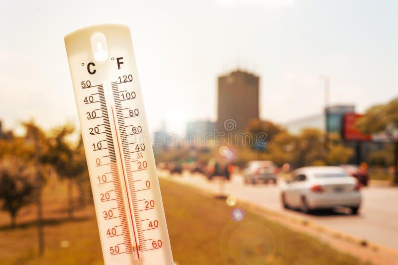 Termómetro delante de los coches y tráfico durante ola de calor fotos de archivo libres de regalías