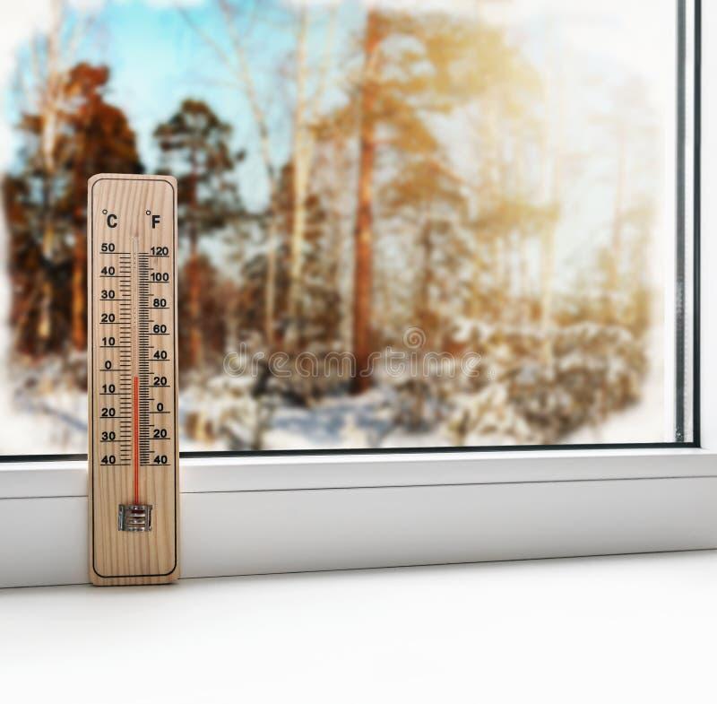 Termómetro en una ventana congelada y un tiempo frío fotos de archivo libres de regalías