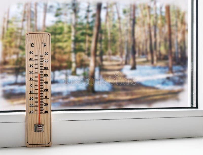 Termómetro en una ventana congelada y un tiempo frío en el st de la primavera foto de archivo