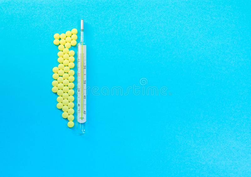 Termómetro médico tradicional y píldoras amarillas fotos de archivo