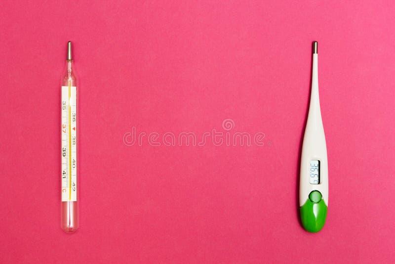 Termômetro análogo e digital em um fundo cor-de-rosa, espaço para o texto fotografia de stock