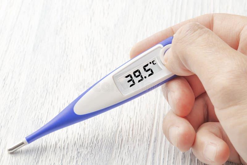 termômetro Branco-azul com uma alta temperatura de 39 5 graus Célsio à disposição imagem de stock