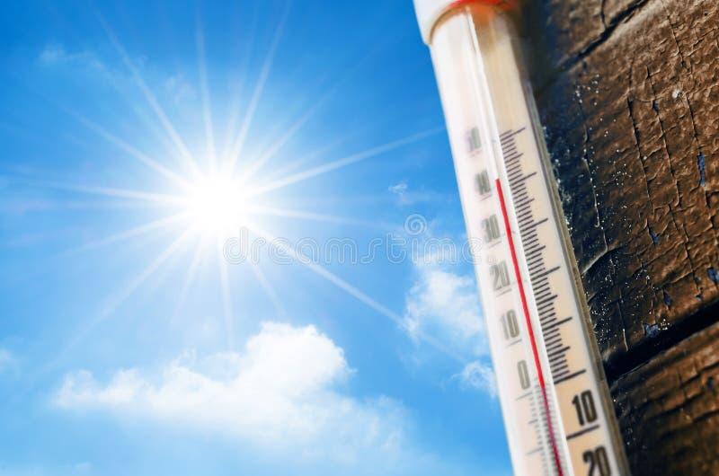 Termômetro com uma leitura de alta temperatura em uma escala, contra um fundo do sol brilhante e de um céu azul com nuvens O conc imagem de stock royalty free
