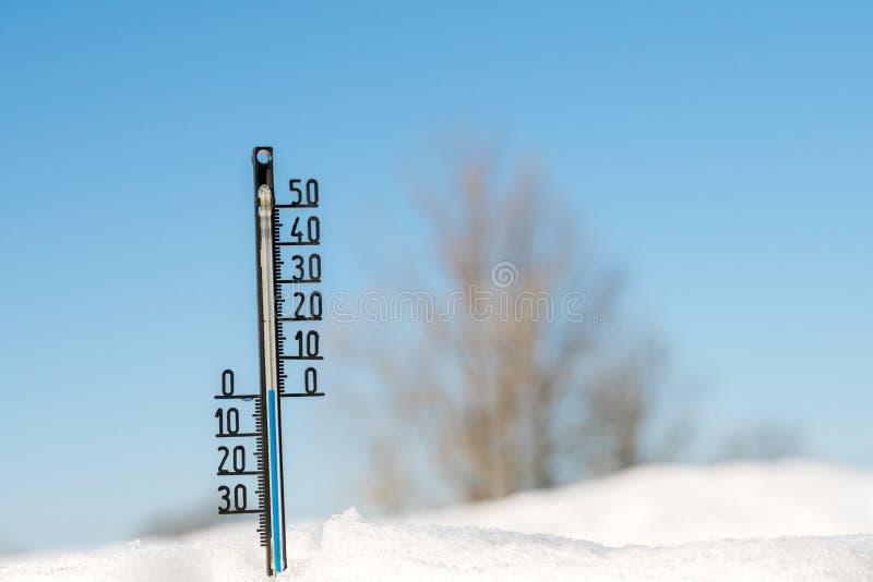 Termômetro da previsão de tempo temperatura da mostra da neve na baixa Céu azul meteorologia fotografia de stock royalty free