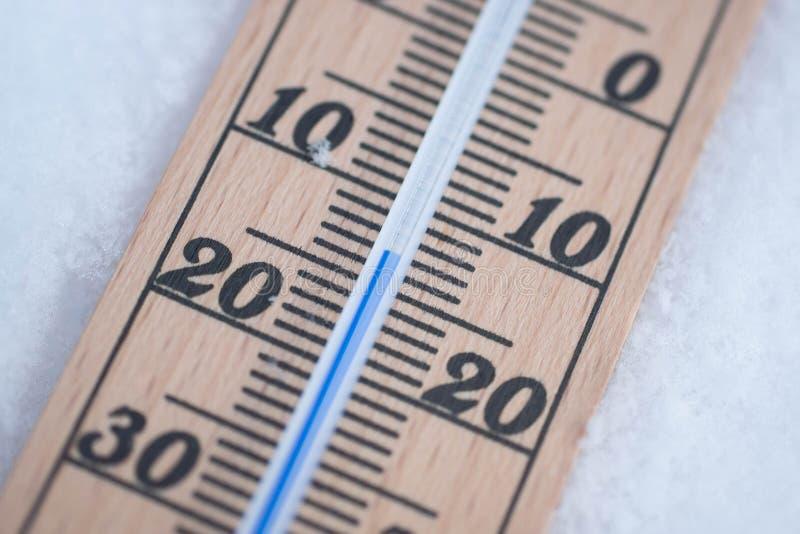 Termômetro de madeira na neve com o tiro do detalhe da temperatura de congelação imagem de stock royalty free