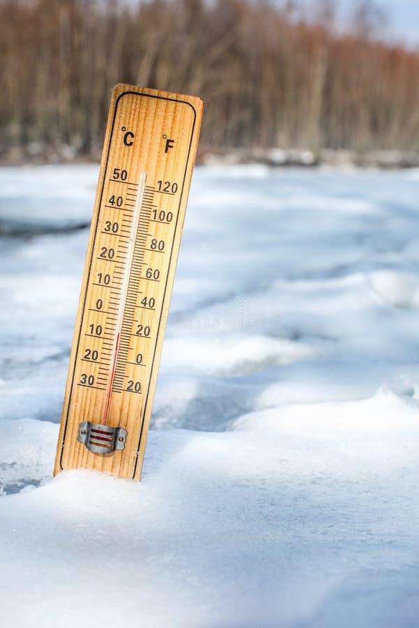 Termômetro de madeira que está na neve fora no dia frio fotografia de stock