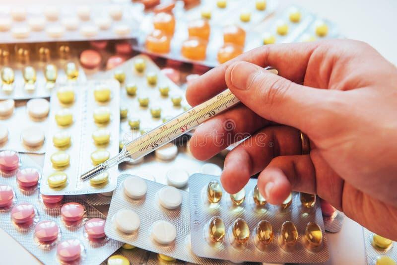 Termômetro e tipos coloridos diferentes de comprimidos Conceito médico da saúde ou das drogas imagem de stock