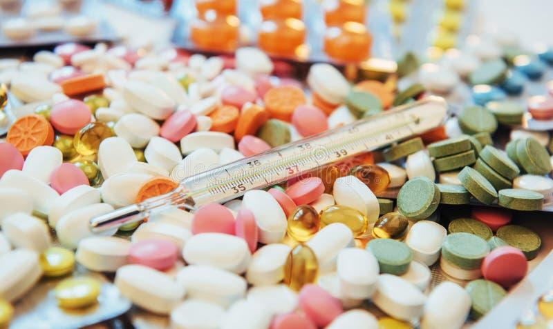 Termômetro e tipos coloridos diferentes de comprimidos Conceito médico da saúde ou das drogas fotos de stock