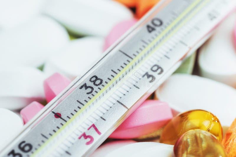 Termômetro e tipos coloridos diferentes de comprimidos Conceito médico da saúde ou das drogas fotografia de stock royalty free