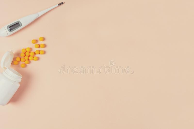 Termômetro eletrônico médico, gotas e comprimidos no fundo cor-de-rosa Conceito dos cuidados médicos Vista superior Copie o espaç fotografia de stock