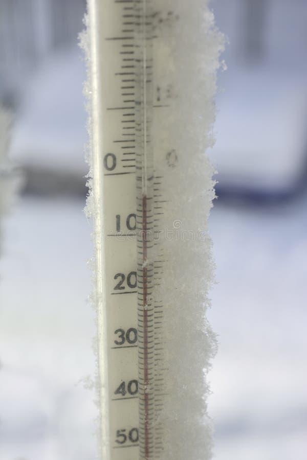 Termômetro em uma geada trazida pela neve foto de stock royalty free