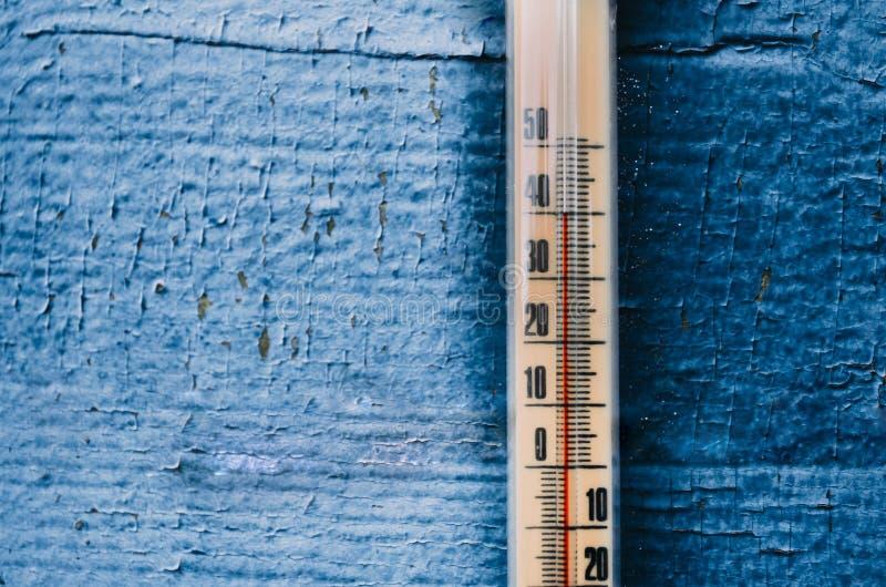 Termômetro na parede de madeira velha, conceito do tempo quente imagem de stock