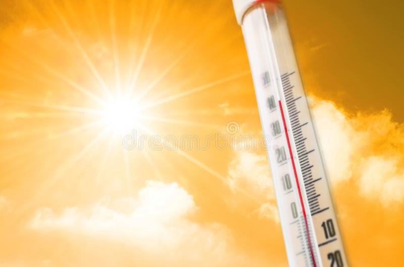 Termômetro na perspectiva de um fulgor quente do amarelo alaranjado das nuvens e do sol, conceito do tempo quente foto de stock