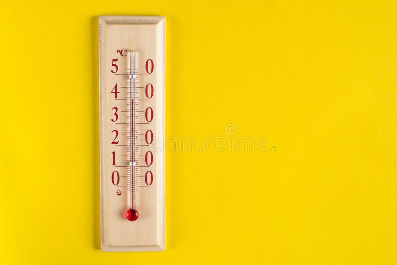 Termômetro para a temperatura do ar de medição no fundo amarelo fotografia de stock