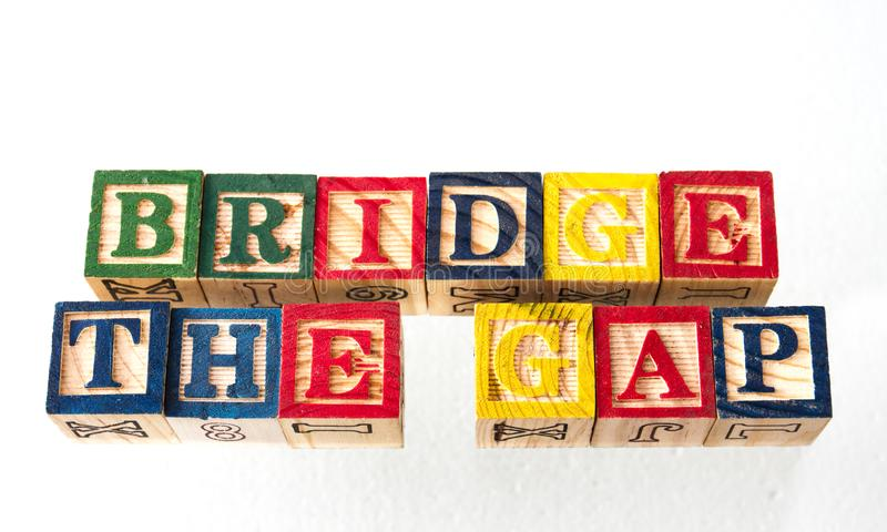 The term for bridge the gap visually displayed. On a white background using colorful wooden toy blocks image with copy space in landscape format royalty free stock images