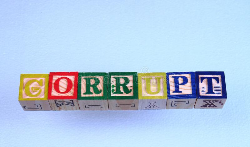 The term corrupt. Displayed visually on a clear background using colorful wooden toy blocks in landscape format with copy space stock photos