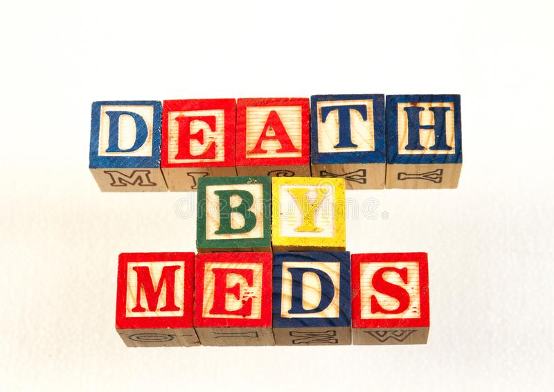 The term death by meds visually displayed. Using colorful wooden toy blocks on a white background image with copy space in landscape format royalty free stock photography