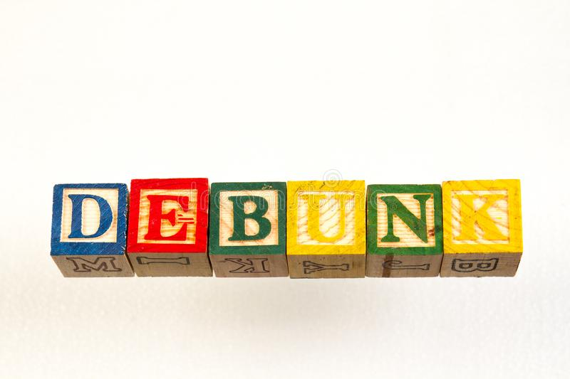 The term debunk visually displayed. Using colorful wooden toy blocks on a white background image with copy space in landscape format royalty free stock photography