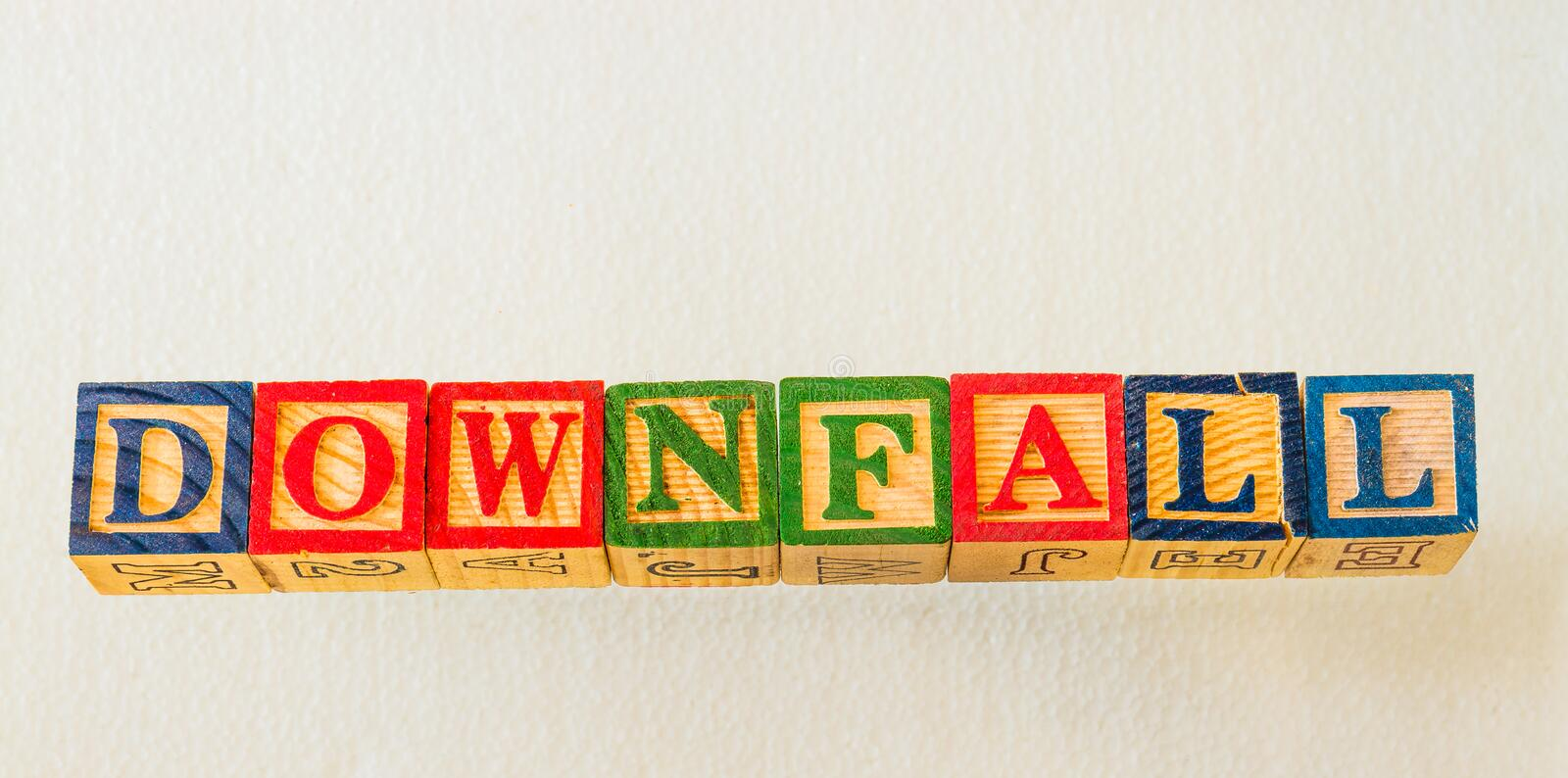 The term downfall visually displayed. On a white background using colorful wooden blocks image with copy space in landscape format stock photos